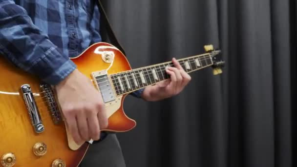 Male guitarist playing on guitar. Professional musician playing on electric guitar. Man performing rock song and playing chords. Guitar lessons