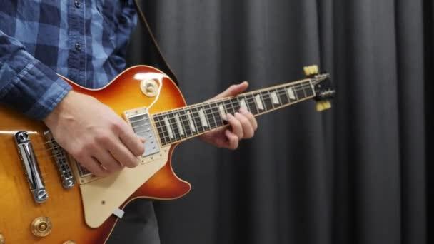Az ember elektromos gitározik. Profi zenész gitáros, aki rockdalt énekel a stúdióban. Fiatal férfi gazdaság pick and play rock and roll