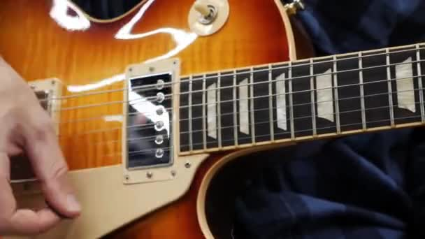 Human fingers playing on electric guitar. Professional musician holding pick and playing chords and solo. Man performing jazz or blues on guitar. Guitar music lessons