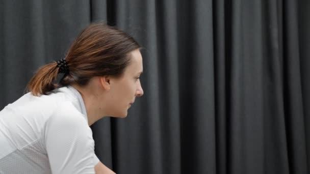 Ženská cyklistika trénink vnitřní zavřít boční pohled. Dívka soustředěný obličej při tréninku na kole