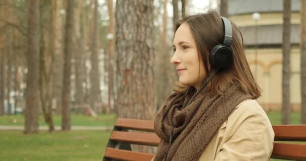 Attractive woman puts on headphones and turns on music while sitting on bench in autumn park enjoying favourite song. Music concept