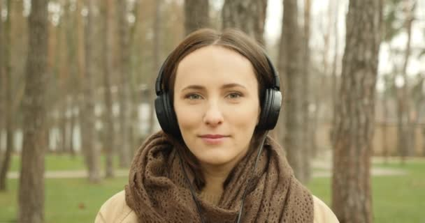 Happy cute woman portrait putting on headphones listening to music and singing her favorite song. Girl enjoying music in earphones