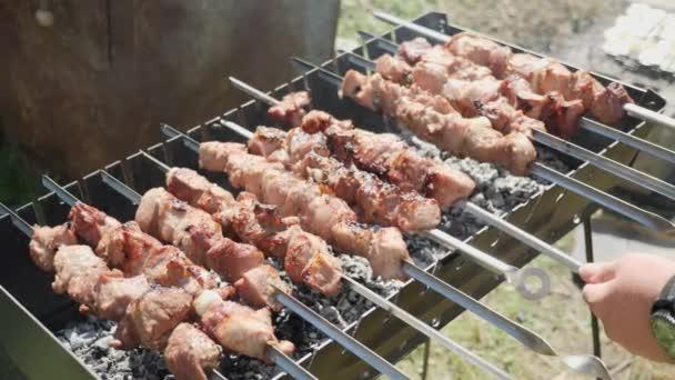 Šéf smaží maso na grilu. Člověk mění maso na špejli. Venkovní gril. Proces přípravy smaženého masa