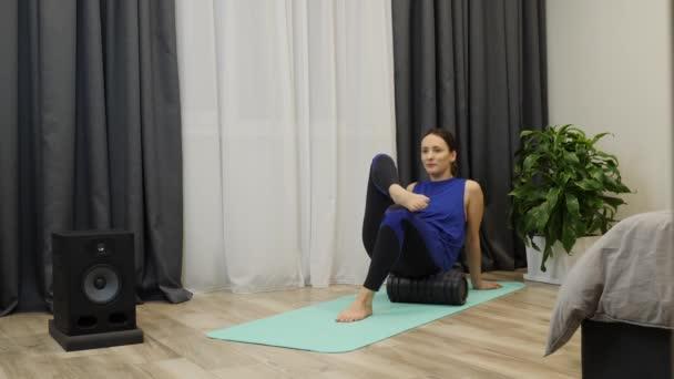 Egy nő rehab gyakorlatokat és resztoratív masszázst végez fascia fitneszgörgővel. Pihent fiatal nő kék sportruházatban masszírozza a test izmait habszivacs görgővel otthon. Lassú mozgás.