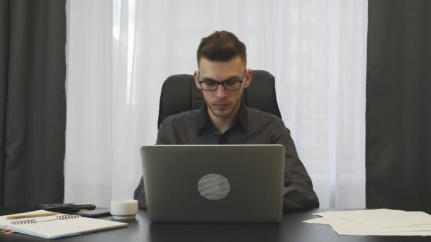 Confident young businessman works on laptop in office. Successful man in glasses working on computer at workplace. Male working on laptop keyboard. Employee doing his job. Man focused on work