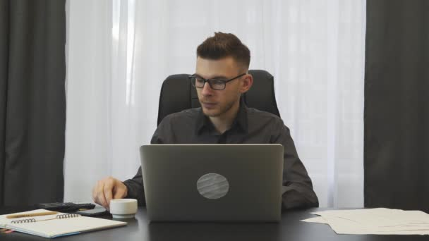 Man drinks coffee espresso in modern office sitting at workplace. Young businessman in suit and glasses drinking coffee at office desk. Male sipping espresso. Business success concept