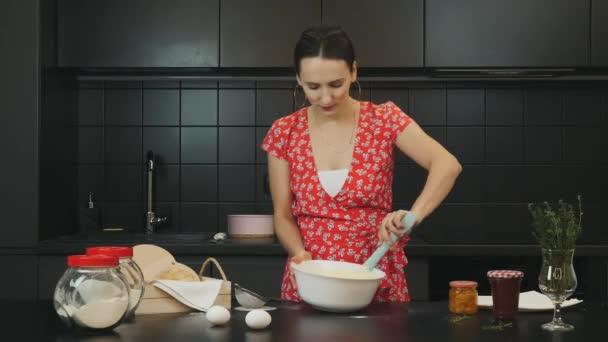 Schöne junge Mutter kocht Weihnachtskuchen in der modernen Küche. Porträt einer attraktiven kaukasischen Frau in der professionellen Küche. Erwachsene Mädchen mischen Zutaten für hausgemachten Kuchen. Hausfrau kocht zu Hause