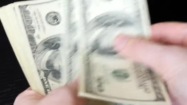 Člověk počítá dolarové bankovky. Ruce počítají americkou stodolarovou hromadu peněz. Zblízka mužské ruce počítají peníze v hotovosti. Finanční koncepce a koncepce plateb