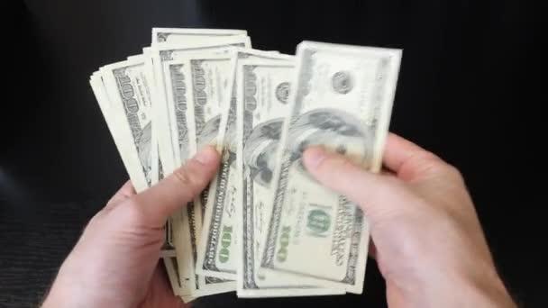 Hände mit Hundert-Dollar-Scheinen stapeln sich. Mann zählt Bargeld auf Bürotisch. Nahaufnahme von amerikanischen Dollars. Amerikanische Währungsumtausch in Bank. Finanzierungs- und Zahlungskonzept