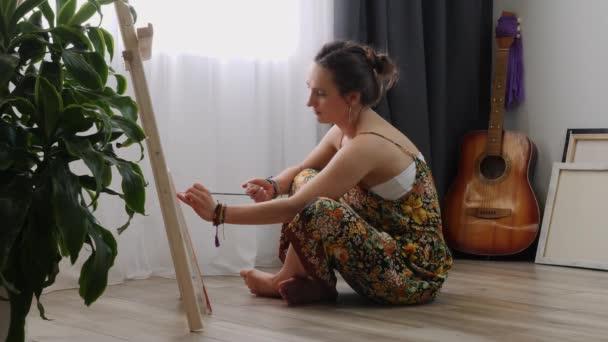 Női művész festés vászonra akril festékek ül a padlón otthon. Fiatal félénk lány rajzol képet ecsettel. Inspiráció. Művészeti akadémia vagy rajziskola