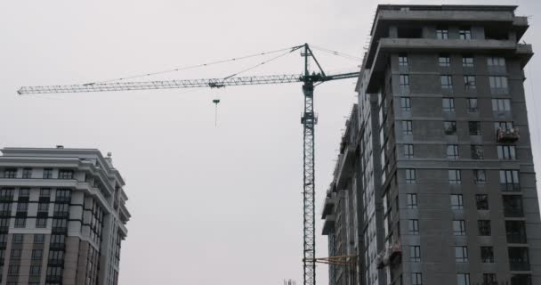 Modern residential complex under construction. Skyscrapers under construction with huge cranes against grey sky and clouds. High crane works on building site with a house