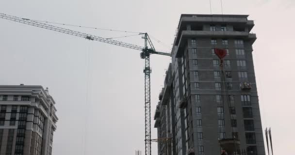 High crane works on construction site. Skyscraper with crane. Workers working on the construction site. Builders build a house. High rise residential complex under construction