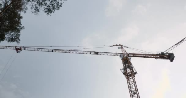 High crane working on construction site. Construction crane against grey sky and clouds. Timelapse of construction.