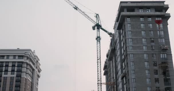 Construction site with crane. High crane works on building. Builders build a house. Crane working on construction site under grey cloudy sky on rainy day