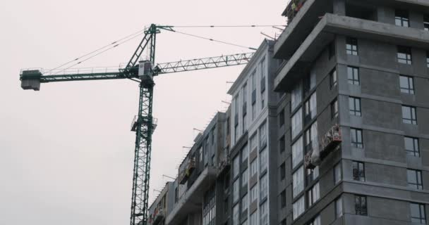 High crane works on building site, close up. Construction process of skyscraper with crane and workers are building house. High rise modern residential complex under construction with huge crane