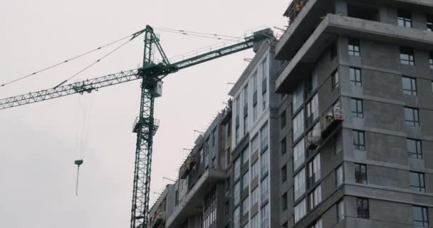 Apartment building under construction with high crane. Builders build house. High crane working on building site