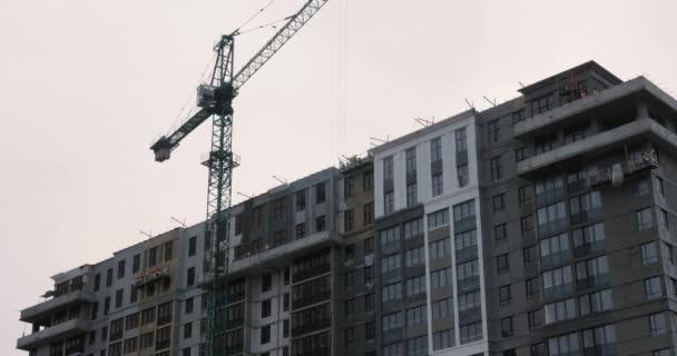 Velký stavební jeřáb pracuje na staveništi. Jeřáb pracuje na staveništi proti šedé zatažené obloze. Výstavba výškového mrakodrapu