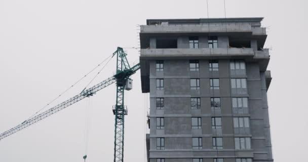 Vysoký stavební jeřáb pracuje na staveništi. Zavřít mrakodrap s jeřábem ve výstavbě. Vysoký jeřáb pracuje na staveništi s domem