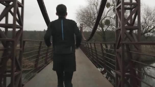 Sportovní hubený muž běží po mostě přes řeku v parku, pohled zezadu. Sportovec běhá venku. Mladý muž v černé punčocháče a bundy jogging a dělat ranní cvičení
