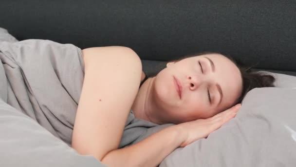 Közelkép egy nő arcáról, aki csukott szemmel fekszik az ágyon. Fiatal, vonzó nő, egyedül alszik az ágyban. A bájos lány portréja párnán alszik.