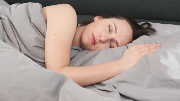 A nő felébred és a kamerába néz, közelről. Bájos, gyönyörű szemű nő az ágyon fekvő kamerát nézi. Portré barna lány fekszik az ágyon, és a kamerába néz