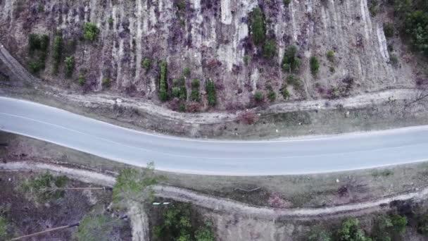 Motivovaný triatlonista jedoucí po prázdné silnici v lese. Izolovaná jízda na kole. Cyklista na silničním kole trénink sám na prázdné dálnici v lese, letecký pohled shora. Kolo jezdec tvrdé šlapání na kole