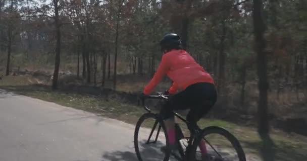 Ženský triatlonista na kole. Žena v helmě na kole. Holčičí kolo na kole. Cyklistika a triatlon koncept