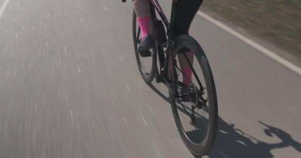 Žena na kole intenzivně jezdí, zblízka. Cyklistické nohy na kole. Žena jezdící na kole. Triatlonista trénuje. Holčičí nohy šlapou na motorce. Koncept triatlonu