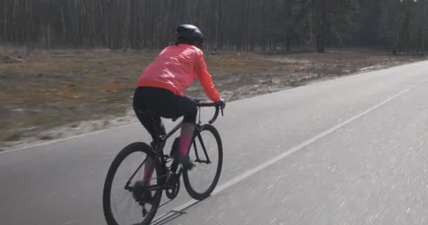 Női biciklizés. Női pedálozás biciklin. A kerékpáros egyedül biciklizik az üres úton. Triatlonos edzés biciklin. Kerékpározás és triatlon koncepció