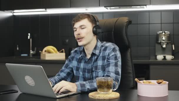Muž ve sluchátkách, který doma dělá videokonferenci. Muž komunikovat s přítelem on-line, aby video hovor. Mladá nezávislá osoba pracující na dálku od domova. Muž na online konferenci z domova