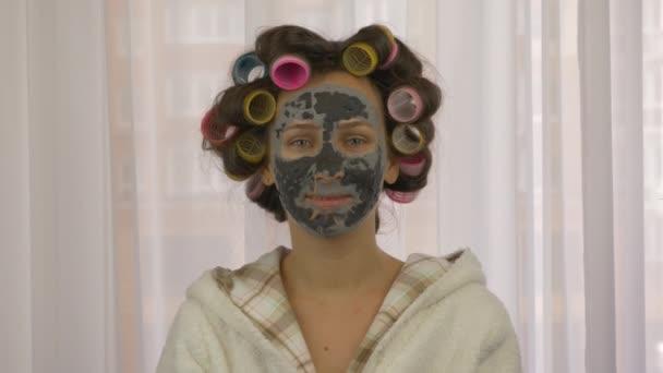Portrét feny s natáčkami na hlavě s hliněnou čistící černou maskou na obličeji, detailní záběr. Mladá žena se stará o pleť doma. Kosmetická léčba. Péče o pleť. Koncepce kosmetiky a krásy