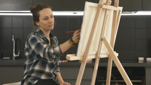 Tehetséges lány festi vászonra a modern konyhában otthon. Portré fiatal női művész festés vászonra segítségével vékony ecset. Női arc rajzol egy képet az állványra. Tehetség. Inspiráció