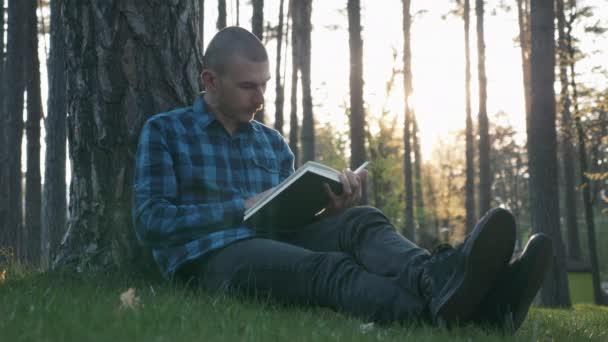 Férfi diák ül a füvön a parkban, és könyvet olvas a gyönyörű naplementében. Portré fiatal diák tanul a parkban és irodalmat olvas, és élvezi a naplementét. A boldog emberek fogalma