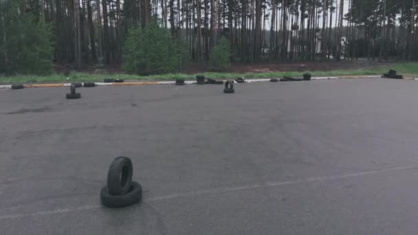 Prázdný asfaltový autodrom se značkami a pneumatikami. Trénink v řízení. Školení o jízdě na parkovišti