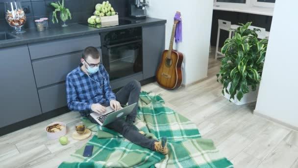 Mladý legrační muž v ochranné masky lékařské tváře poslech hudby ze sluchátek a baví se, hraje na virtuální bicí a kytaru, chatuje online s přáteli a odpovídá na e-maily