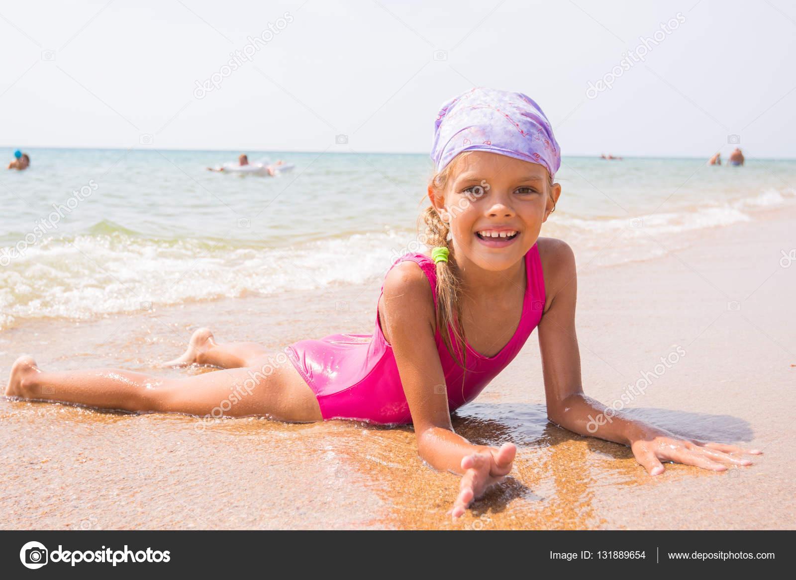 Chica feliz tumbado en la arena cerca del agua en la playa y ...