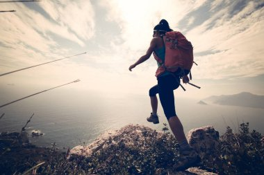 hiker climbing on mountain peak