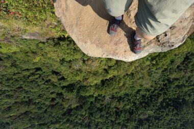 female legs on mountain peak