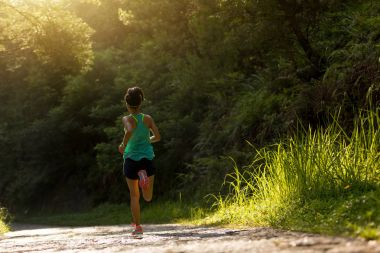 Young fitness woman athlete running on forest trail