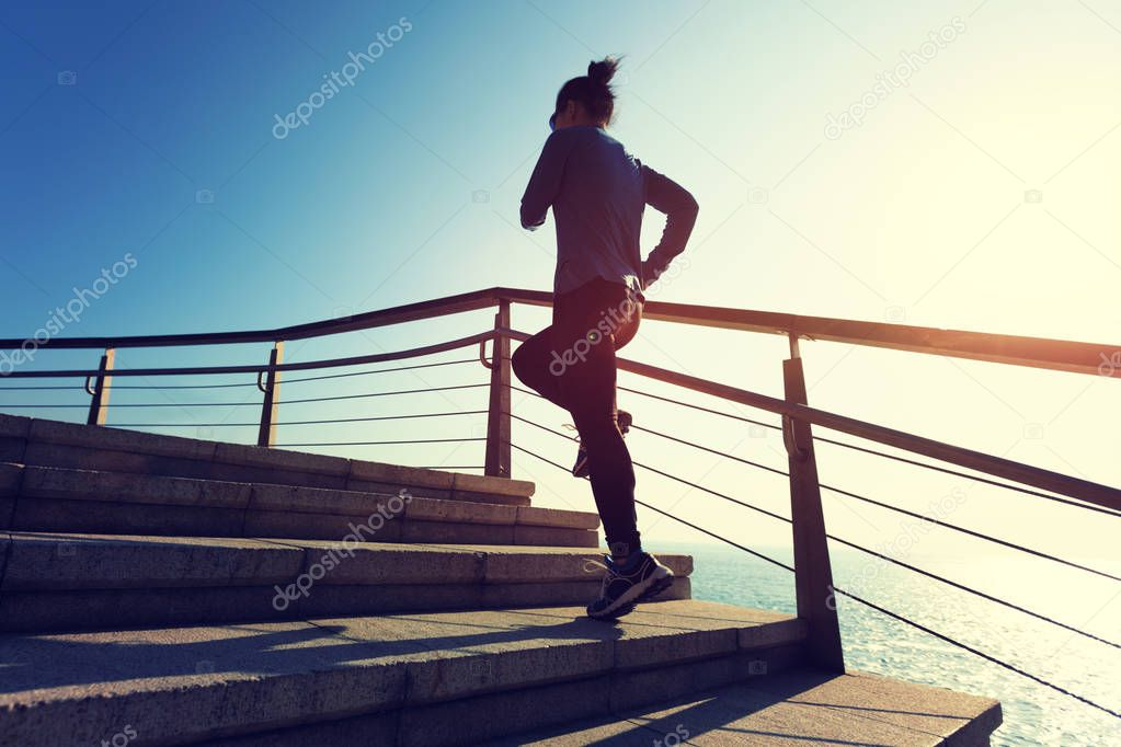 sporty young woman running upstairs on coast trail