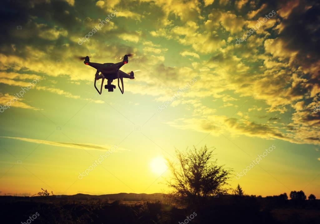 flying drone in the sky during sunset
