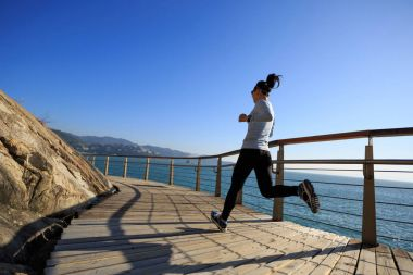sporty female jogger running on seaside boardwalk