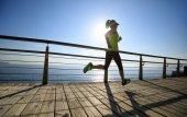 Fotografie Sportovní fitness žena běží na přímořské promenádě během východu slunce