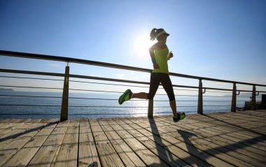 Sporty fitness woman running on seaside boardwalk during sunrise