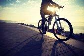 Fotografie cyklista jízdní kolo v cestě pobřeží sunrise