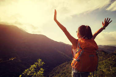 happy woman backpacker looking at the mountains with arms outstretched on mountain top during sunrise