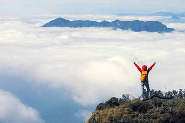 successful hiker with arms outstretched on mountain