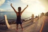 Dívka s rukama na letní. Krásný inspirující krajinu a moře s dívkou a rukama nad hlavou na východ slunce
