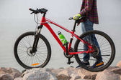 Fotografie woman cyclist with mountain bike on seaside