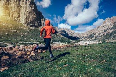 woman trail runner running on beautiful mountains